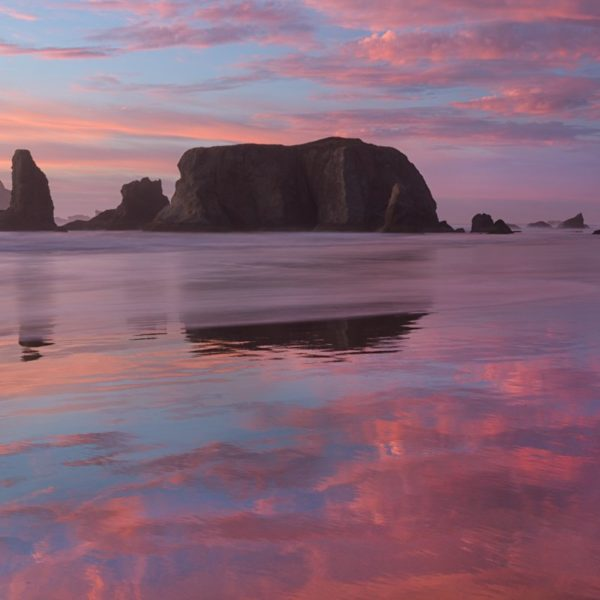 sea stacks and clouds reflecting on the beach